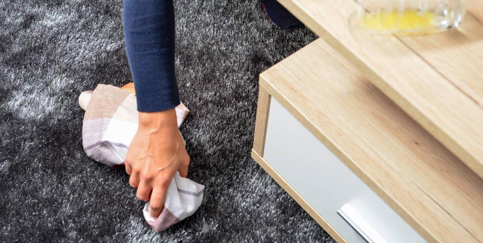 Person reinigt Teppich mit einem Tuch.jpg