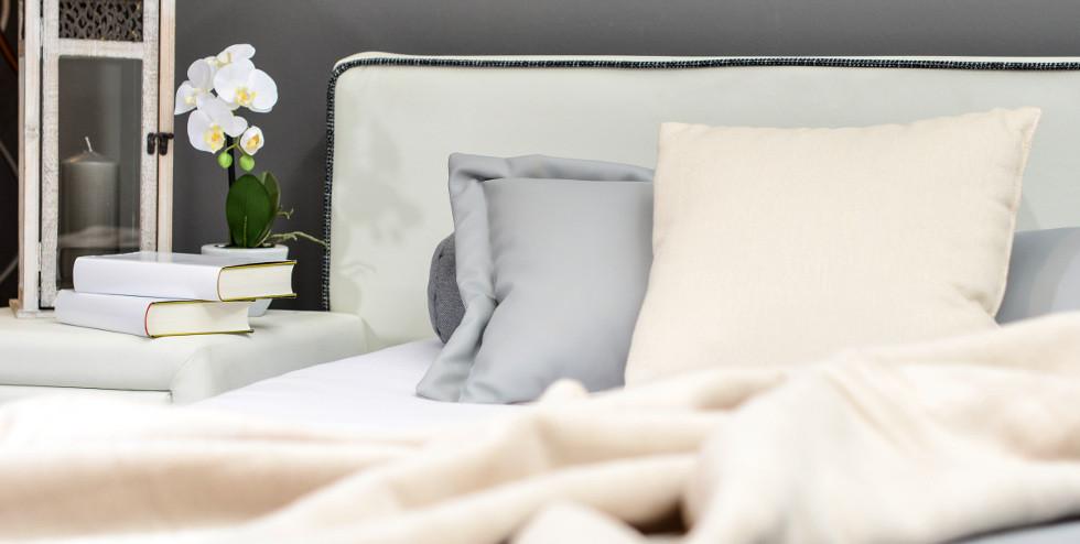 Detailaufnahme eines Bettes mit Tagesdecke und Deko in sanften Farben.jpg