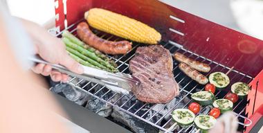 Fleisch, Gemüse und Würstchen auf dem Griller zubereiten