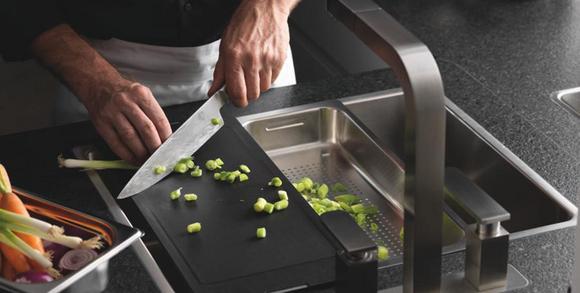 Mann schneidet Gemüse bei der Küchenspüle