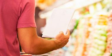 mann im supermarkt mit einkaufsliste in der hand