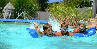 Drei Kinder liegen auf Möbelix Luftmatratze im Pool.jpg