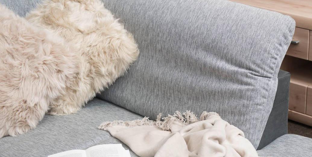 Stoffcouch in grauem Farbton mit flauschigen Zierkissen.jpg